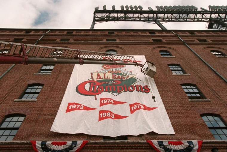 From a cherry picker: Charles Wong works to attatch a banner to the warehouse at Orioles Park at Camden Yards in preparation for the 1997 American League Division Series playoff game against Seattle. (Doug Kapustin/Baltimore Sun Photo)