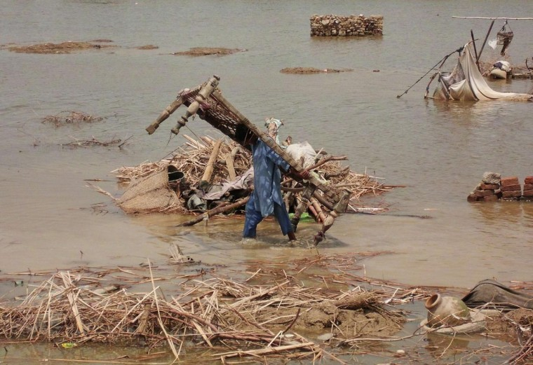 """A man carries a """"charpoy"""" (rope bed) as he wades through flood waters in Dera Allah Yar, located in the Jaffarabad district of Balochistan province, August 6, 2013. Monsoon rains have claimed more than 80 lives in Pakistan, according to local media on Monday. (Amir Hussain/Reuters)"""