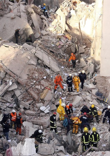 Rescue workers remove a body from among the rubble after an explosion caused by a gas leak tore through a 10-story building in Rosario city, in the province of Santa Fe. Twelve people have died, 60 injured and 15 remain missing as firefighters and rescue workers continue to search for people believed to be trapped in the area, according to local authorities. (Marcelo Masuelli/Reuters)