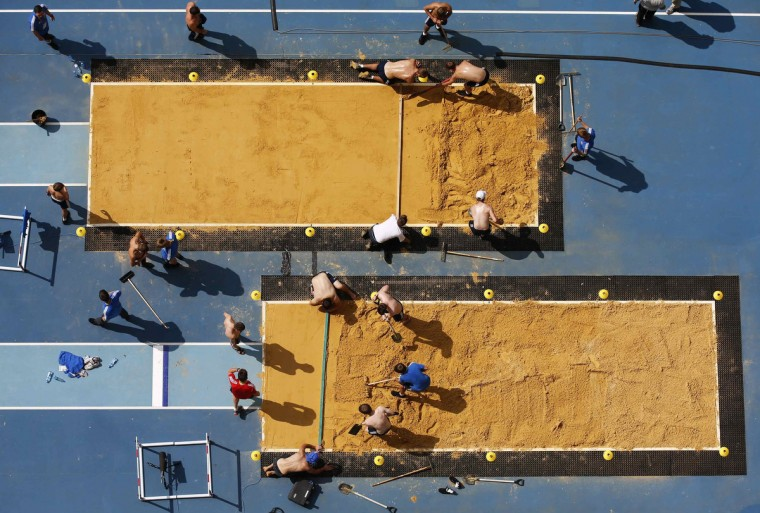 Volunteers prepare the sandpit for the 14th IAAF World Championships at the Olympic stadium in Moscow. The event will be held from August 10 to 18. (Fabrizio Bensch/Reuters)