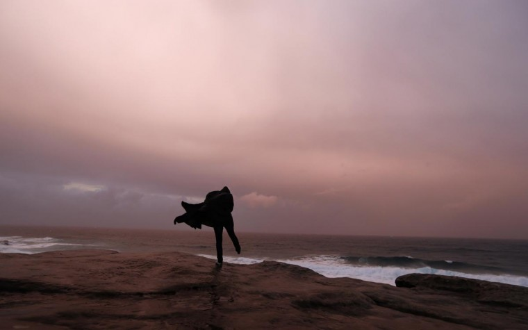 A woman plays on the edge of a cliff on a rainy winter afternoon at Bronte beach in Sydney August 8, 2013. (Daniel Munoz/Reuters)