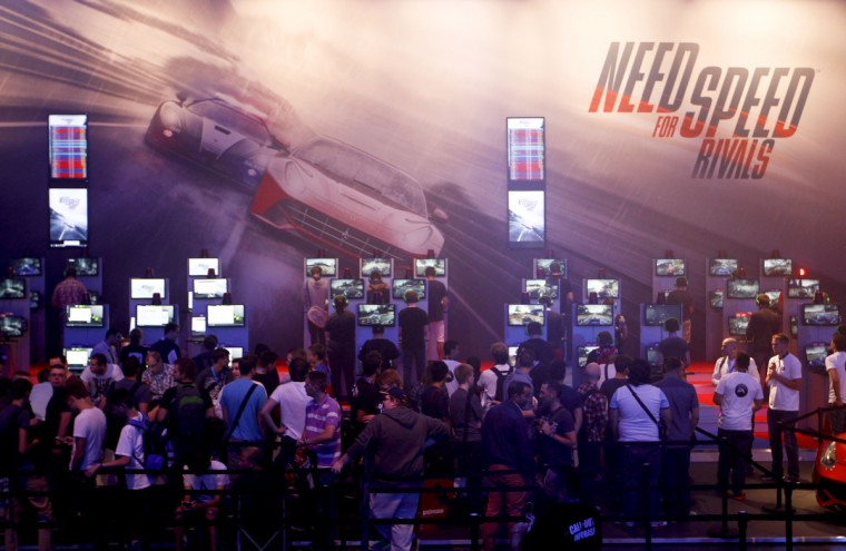Visitors play Need for Speed Rivals game at the Electronic Arts EA exhibition stand during the Gamescom 2013 fair in Cologne. (Ina Fassbender/Reuters)
