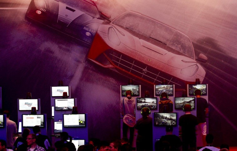 Visitors play Need for Speed Rivals game at the Electronic Arts EA exhibition stand during the Gamescom 2013 fair. (Ina Fassbender/Reuters)