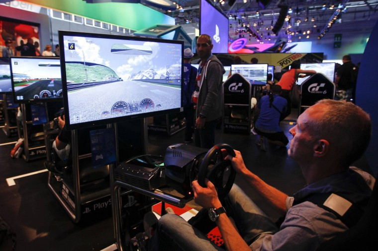 "Visitors play ""Gran Turismo 6 "" at the Sony exhibition stand during the Gamescom 2013 fair. (Ina Fassbender/Reuters)"