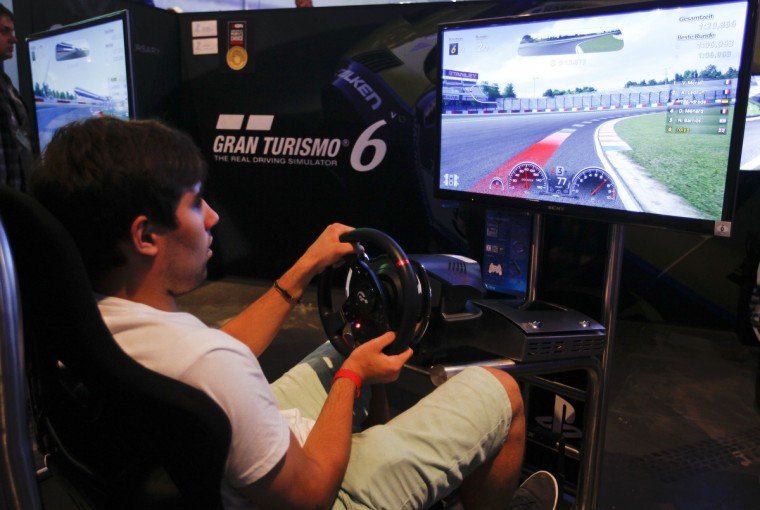 "A visitor plays ""Gran Turismo 6 "" at the Sony exhibition stand during the Gamescom 2013 fair in Cologne. (Ina Fassbender/Reuters)"