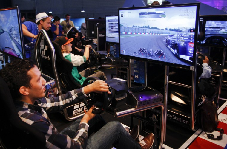 "Visitors play ""Gran Turismo 6 "" at the Sony exhibition stand during the Gamescom 2013 fair in Cologne. (Ina Fassbender/Reuters)"