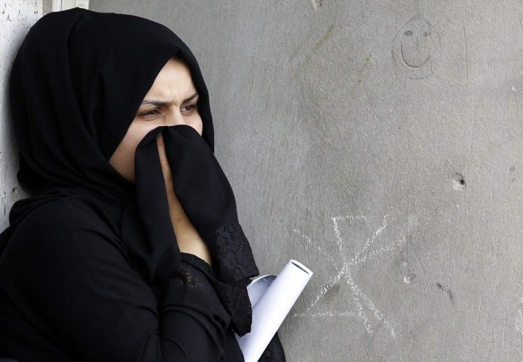 A woman watches as Ali Isa Albasri's funeral procession passes through a street in the village of Sitra, south of Manama in Bahrain, August 2, 2013. Mahmood Abbas Alaradi and Albasri died when the car they were travelling in hit a vehicle while they were being chased by police, according to opposition. Police issued a media statement saying that the police have nothing do to with the accident and stated that it was a fatal road accident. Both victims were buried in the village on Friday. (Hamad I Mohammed/Reuters)