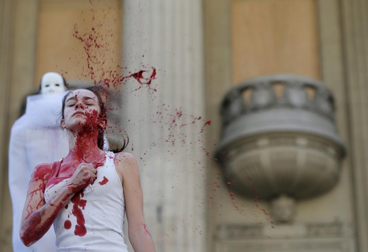 An actress splashes red paint on herself during a protest by Grupo Fazendo Certo (Group Doing Right) and non-governmental organization (NGO) Rio de Paz (Rio of Peace) in support of victims of violence, in front of the Rio de Janeiro State Assembly August 13, 2013. According to Rio de Paz, 35,000 victims of violence have been missing in the Rio de Janeiro state since 2007. (Sergio Moraes/Reuters)