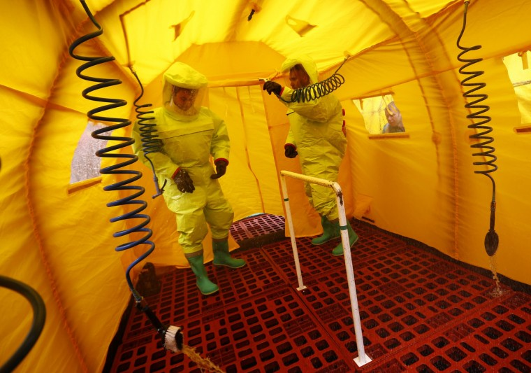 Fire officers are sprayed down in a decontamination tent during a mock terrorism exercise at the International Convention Centre in Birmingham, central England. The exercise, involving the emergency services, is the first of three taking place across Europe as part of an EU funded initiative to improve the preparedness and resilience of member states to a terrorist attack. (Darren Staples/Reuters photo)