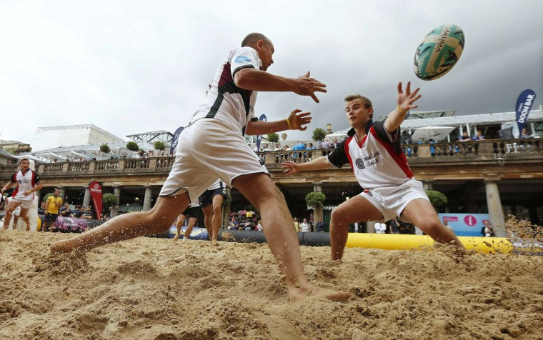 Competitors from Incentive FM Group (left) and Jones Lang LaSalle play in a Beach Rugby tournament in Covent Garden in London August 9, 2013. The two-day tournament features competitors from the corporate sector and traditional rugby clubs and is raising funds for Restart, the official charity of the Rugby Players' Association. (Suzanne Plunkett/Reuters)