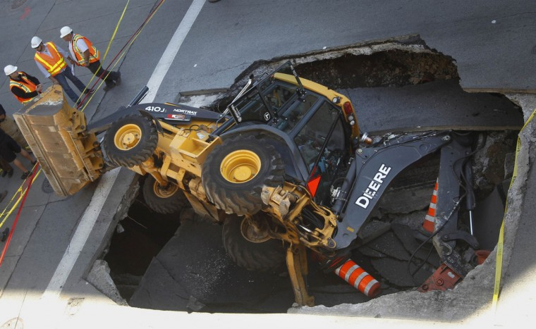 A construction vehicle lies where it was swallowed by a sinkhole on Saint-Catherine Street in downtown Montreal. (Christinne Muschi/Reuters)