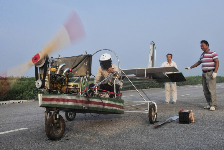 Ding Shilu (L) tests the engine of his self-made aircraft before conducting a test flight on the outskirts of Shenyang, Liaoning province. Ding, a 65-year-old migrant worker, spent around 2,000 yuan ($327) to build this 5-metre-long, 4.5-metre-high plane using components from motorcycles and electric bicycles. Ding failed his fourth test flight on Tuesday since he started his project four years ago, local media reported. (Sheng Li/Reuters)