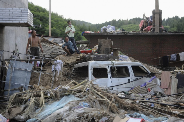 People stand on ruins after downpours ravaged Nankouqian township in Fushun, Liaoning province. The floods which began August 15 have killed 54 people and leaving 97 missing in Fushun so far, according to local reports. (China Daily/Reuters)