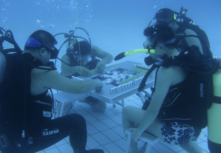 Diving instructors play mahjong in a swimming pool in Xiangtan, Hunan province. According to local media, the trainers re-invented the game of mahjong by playing it under water in a 5.5-metre-deep pool to escape from the summer heat, and since then more than 10 divers have been playing the game. China's top meteorological authority on Tuesday continued to warn of prolonged heat that has afflicted central and eastern China since July, Xinhua News Agency reported. (Reuters)