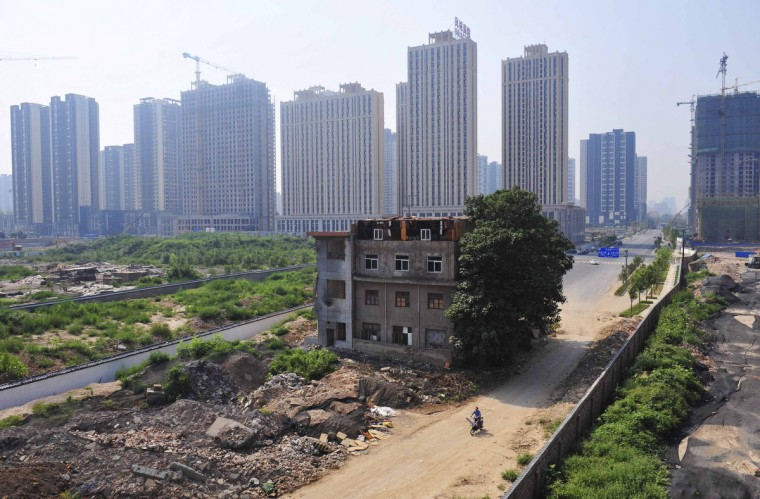 A man rides his bicycle past a partially demolished building in the middle of a street next to residential construction sites in Xi'an. A family of 7 still lived in the three-story building without electricity and water after a demolition project in the region took place in 2010. (Stringer/Reuters photo)
