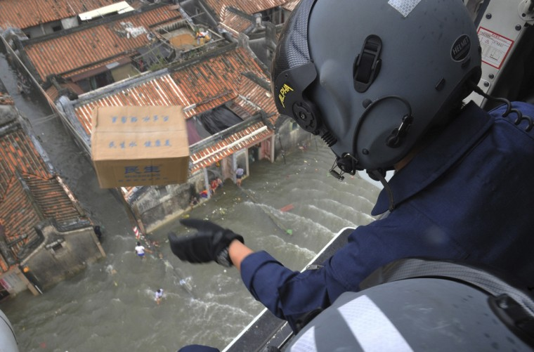 A rescue worker throws a box containing water out of a helicopter above a flooded area in Shantou, Guangdong province. Flooding triggered by rainstorms has ravaged the city for the last few days, affecting 772,000 people across 11 townships, according to local media. (China Daily/Reuters)