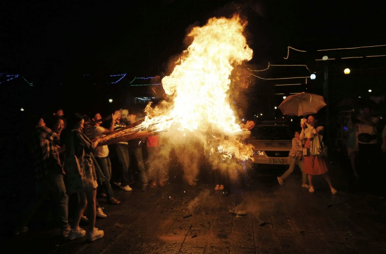 People hold torches as they celebrate the ethnic Bai people's traditional Torch Festival in Dali, Yunnan province, August 1, 2013. The annual Torch Festival typically starts at sunset on the 25th day of the sixth month of the Chinese lunar calendar, during which people worship, light, play and dance with torches to pray for good harvests and good luck in the future. (William Hong/Reuters Photo)