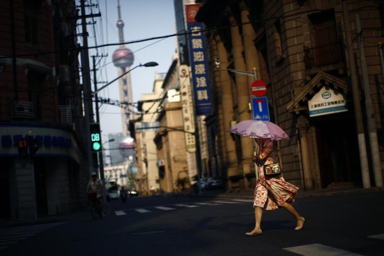 A woman uses an umbrella to protect herself from the sun as she crosses a busy street in downtown Shanghai August 6, 2013. The temperature in Shanghai rose to 41.1 degrees Celsius (106 degrees Fahrenheit) on Tuesday, according to local media. (Carlos Barria/Reuters)