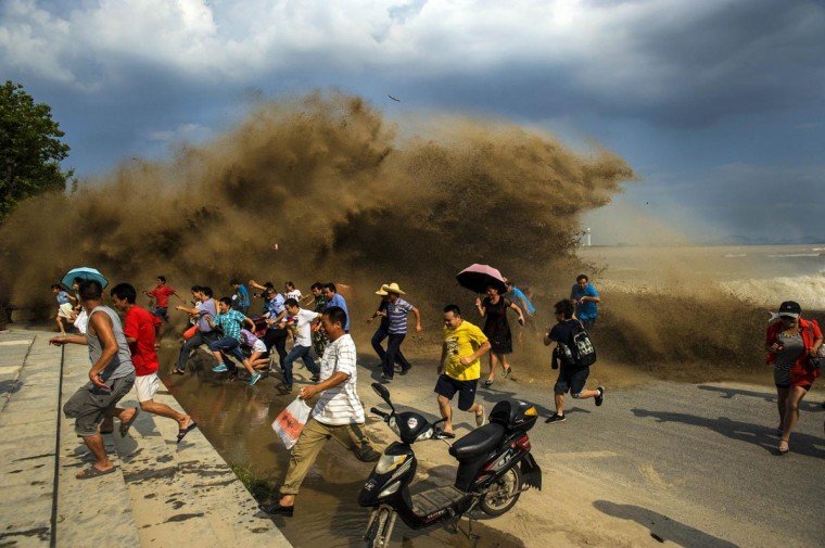 Visitors run away as waves from a tidal bore surge past a barrier on the banks of Qiantang River, in Hangzhou Zhejiang province, August 24, 2013. Picture taken August 24, 2013. (Stringer/Reuters)