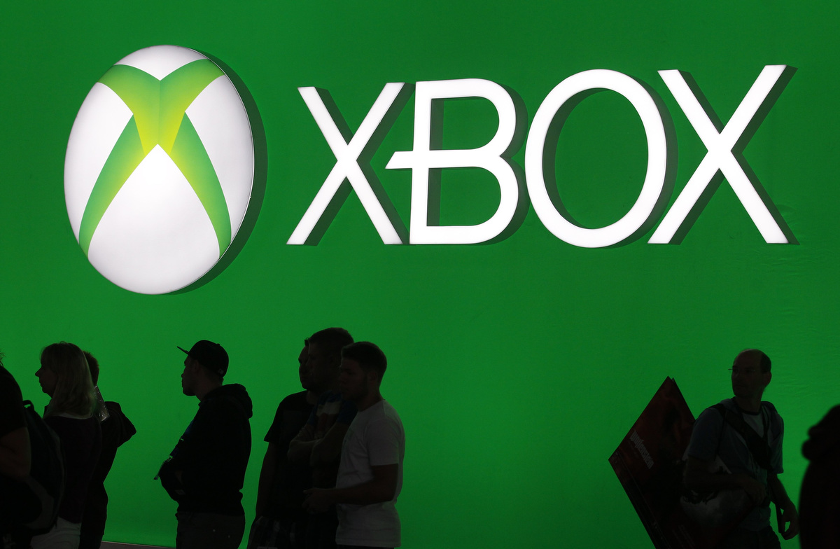 Modern Exhibition Stand Xbox One : Visitors walk past an advertising placard of the xbox one