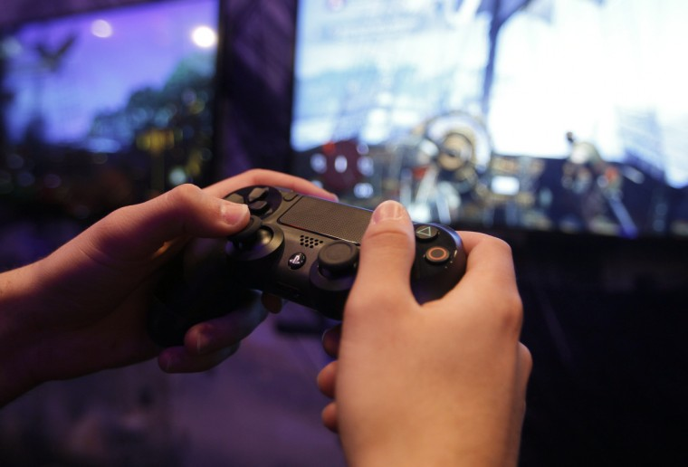 A visitor plays a Playstation 4 at the Sony exhibition stand during the Gamescom 2013 in Cologne. (Ina Fassbender/Reuters)