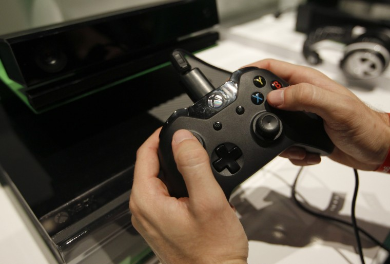 A visitor plays the Xbox One at the Microsoft Games exhibition stand during the Gamescom 2013 fair in Cologne. (Ina Fassbender/Reuters)