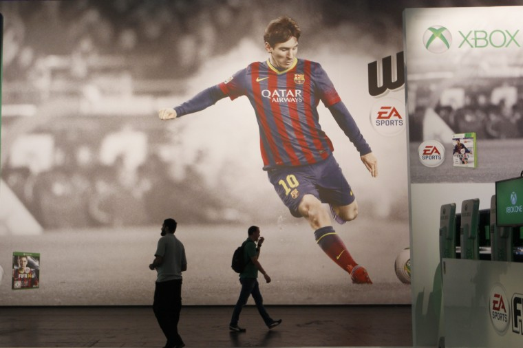 "Visitors walk past an advertising placard ""FIFA 14"" during the Gamescom 2013 fair in Cologne. (Ina Fassbender/Reuters)"