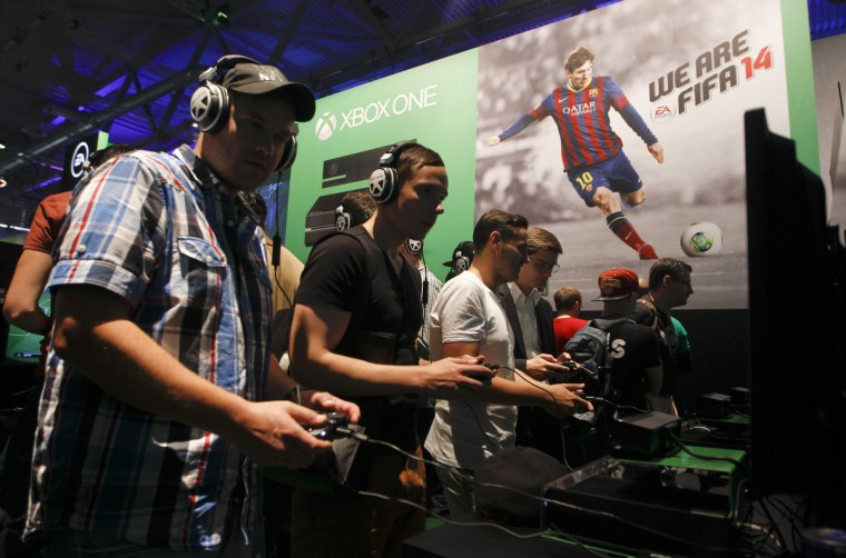 "Visitors play ""FIFA 14"" with the Xbox One at the Microsoft Games exhibition stand during the Gamescom 2013 fair in Cologne. (Ina Fassbender/Reuters)"