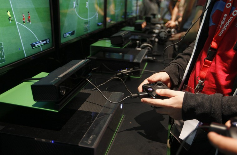 "Visitors play ""FIFA 14"" with the Xbox One at the Microsoft Games exhibition stand during the Gamescom 2013 fair in Cologne, Germany. (Ina Fassbender/Reuters)"
