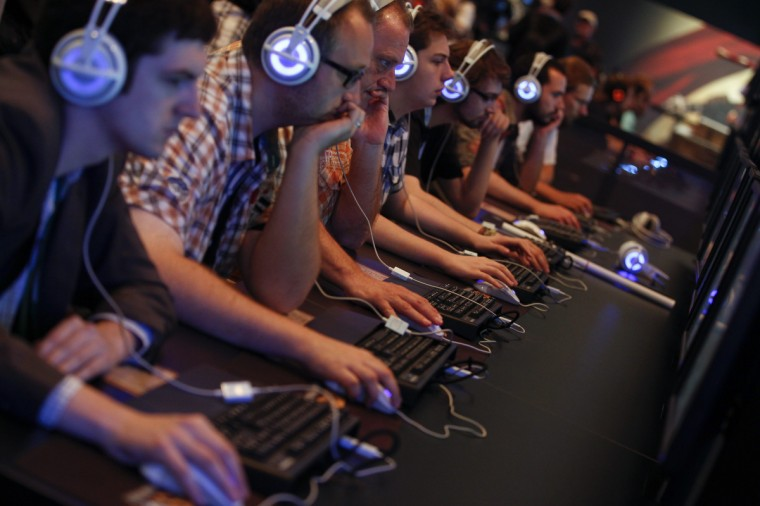 "Visitors play ""Hearthstone"" at the World of Warcraft exhibition stand during the Gamescom 2013 fair in Cologne, Germany. (Ina Fassbender/Reuters)"