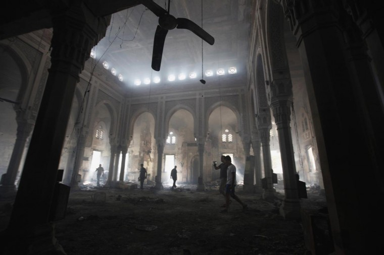 People walk inside the burnt Rabaa Adawiya mosque, the morning after the clearing of a protest which was held around the mosque, in Cairo, August 15, 2013. (Mohamed Abd El Ghany/Reuters)