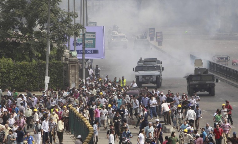 Riot police vehicles fire tear gas at members of the Muslim Brotherhood and supporters of deposed Egyptian President Mohamed Mursi, around Cairo University and Nahdet Misr Square, where they are camping in Giza, south of Cairo August 14, 2013. (Mohamed Abd El Ghany/Reuters)