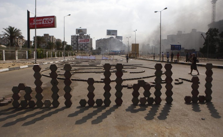 "Bricks form the Arabic words: ""There is no god but Allah"" as smoke rises during clashes between riot police, and members and supporters of the Muslim Brotherhood, at Rabaa al-Adawiya Square, where the latter had been camping, in Cairo August 14, 2013. (Amr Abdallah Dalsh/Reuters)"