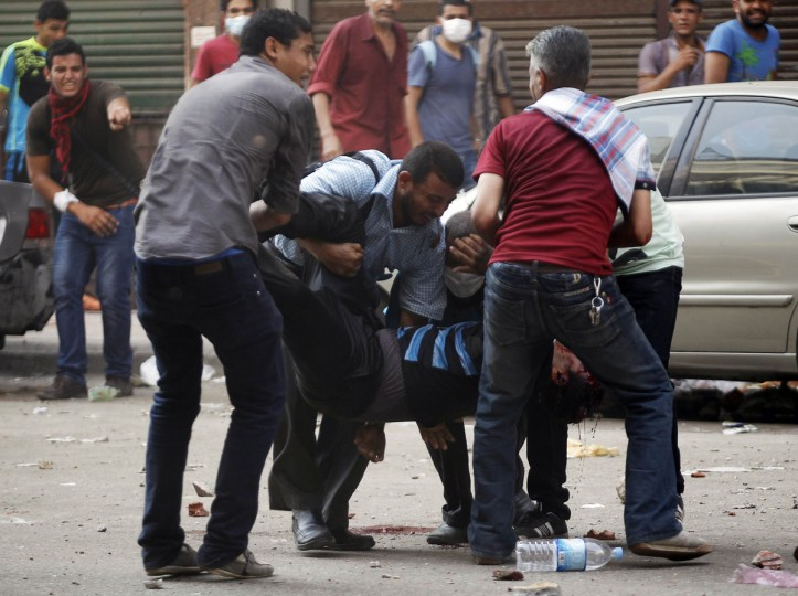 Protesters who support ousted Egyptian President Mohamed Morsi carry an injured demonstrator during clashes outside Azbkya police station at Ramses Square in Cairo, August 16, 2013. About 50 people were killed in protests in Cairo on Friday, security officials said. Thousands of supporters of Morsi have been staging nationwide protests against a security crackdown on Islamists. (Amr Abdallah Dalsh/Reuters)