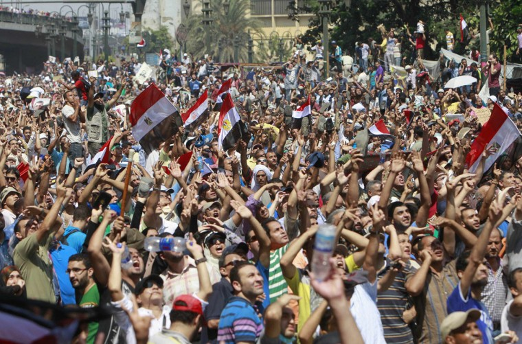 """Supporters of deposed Egyptian President Mohamed Morsi shout slogans and wave Egyptian flags during a protest outside Al-Fath Mosque in Cairo August 16, 2013. Thousands of supporters of ousted President Mohamed Morsi took to the streets on Friday, urging a """"Day of Rage"""" to denounce this week's assault by security forces on Muslim Brotherhood protesters that killed hundreds. The army deployed dozens of armored vehicles on major roads in Cairo, and the Interior Ministry has said police will use live ammunition against anyone threatening state installations. (Mohamed Abd El Ghany/Reuters)"""