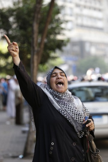 "A woman shouts slogans as supporters of deposed Egyptian President Mohamed Morsi take part in a protest outside Al-Fath Mosque in Ramses Square, in Cairo August 16, 2013. Thousands of supporters of Morsi took to the streets on Friday, urging a ""Day of Rage"" to denounce this week's assault by security forces on Muslim Brotherhood protesters that killed hundreds. The army deployed dozens of armored vehicles on major roads in Cairo, and the Interior Ministry has said police will use live ammunition against anyone threatening state installations. (Youssef Boudlal/Reuters)"