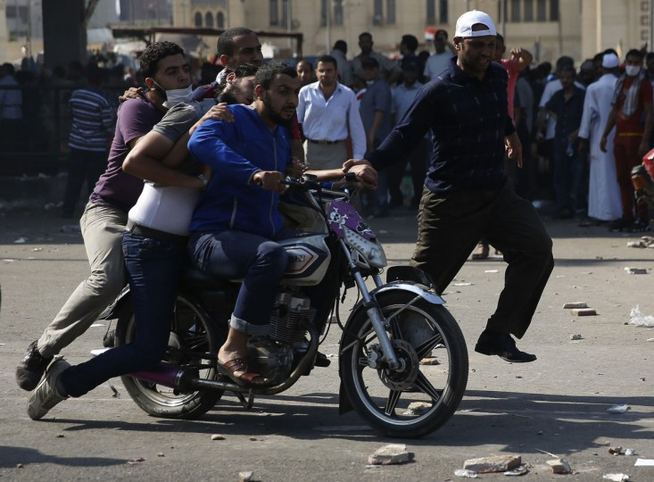 """An injured supporter of ousted Egyptian President Mohamed Morsi is rushed from clashes in Ramses Square in Cairo August 16, 2013. Muslim Brotherhood protests plunged into violence across Egypt on Friday, with around 50 killed in Cairo alone on a """"Day of Rage"""" called by Islamist supporters of Morsi to denounce a police crackdown. (Steve Crisp/Reuters)"""