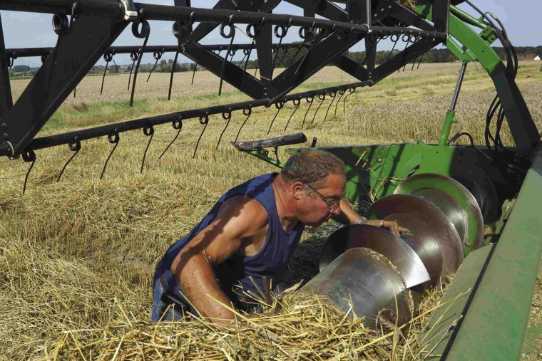 A French farmer inspects the blades of his combine as he harvests wheat in a field in Raches, near Douai, northern France, which has reached maturity due to warm summer temperatures August 2, 2013. (Pascal Rossignol/Reuters)