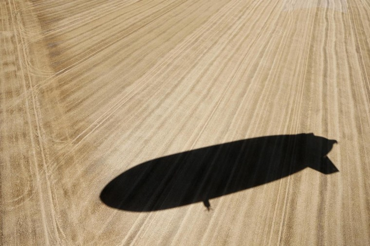 The shadow of a semi-rigid and helium-filled airship, the Zeppelin NT, is cast on a harvested wheat field as it approaches an airport outside Cergy-Pointoise, near Paris, August 4, 2013. The Zeppelin NT is powered by three pivoting motors and measures 246 ft long, 57 feet high, and 64 feet wide. It also has a cabin that fits 12 passengers and will fly tourists at an altitude of 984 feet over the countryside. Airship Paris, which runs the Zeppelin NT, will propose three different flights for tourists in the Paris region. (John Schults/Reuters)
