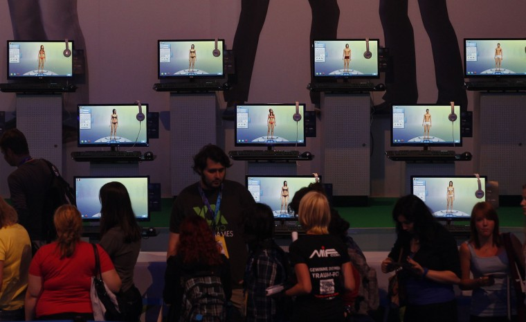 "Visitors play ""Sims 4"" at the Electronic Arts EA exhibition stand during the Gamescom 2013 fair in Cologne, Germany. (Ina Fassbender/Reuters)"