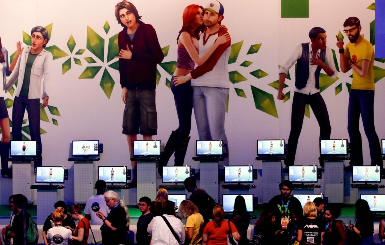 "Visitors play ""Sims 4"" at the Electronic Arts EA exhibition stand during the Gamescom 2013 fair in Cologne. (Ina Fassbender/Reuters)"