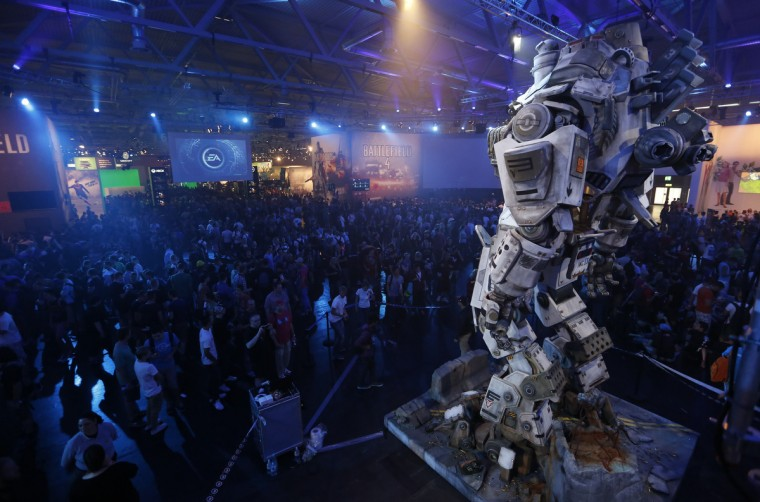 Visitors arrive at the Electronic Arts EA exhibtion stand during the Gamescom 2013 fair in Cologne, Germany. (Ina Fassbender/Reuters photo)