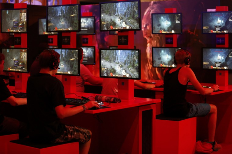 "Visitors play ""Diablo"" at the Blizzard exhibition stand during the Gamescom 2013 fair in Cologne. (Ina Fassbender/Reuters photo)"