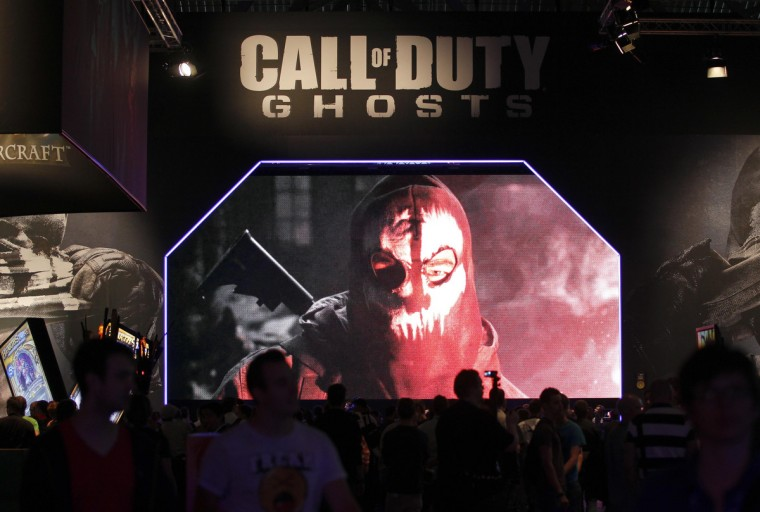 "Visitors look at a presentation of ""Call of Duty Ghosts"" at an exhibition stand during the Gamescom 2013 fair in Cologne. (Ina Fassbender/Reuters)"