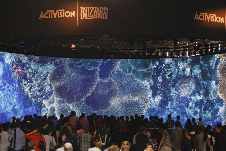 Visitors look at a presentation at the ActiVision Blizzard exhibition stand during the Gamescom 2013 fair in Cologne, Germany. (Ina Fassbender/Reuters)