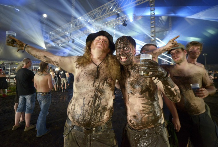 Heavy metal fans covered with mud pose for photographers during the 24th Wacken Open Air Festival in Wacken. (Fabian Bimmer/Reuters)