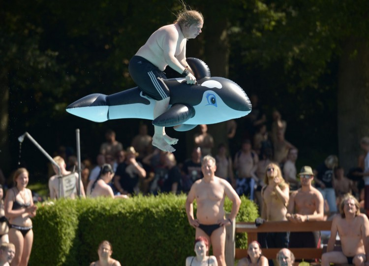 A heavy metal fan, sitting on a plastic whale float, jumps into a swimming pool during the 24th Wacken Open Air Festival in Wacken, August 2, 2013. More than 75,000 heavy metal fans are expected to attend the largest heavy metal festival in the world, organizers said. (Fabian Bimmer/Reuters)