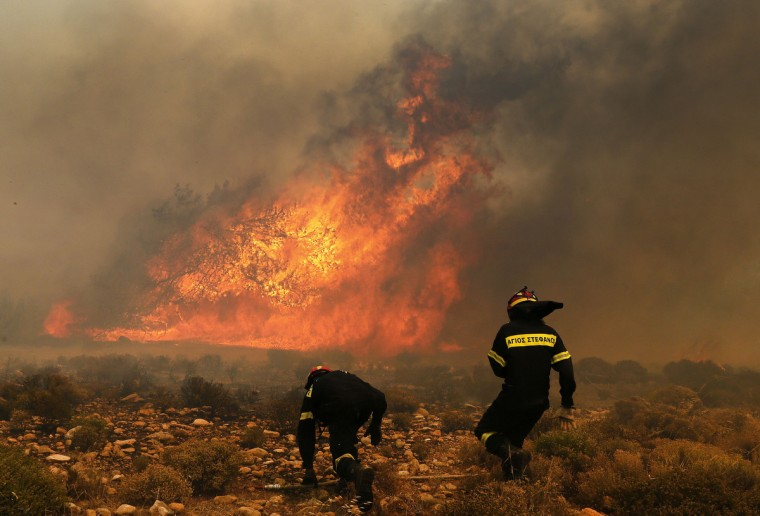 A Greek firefighter runs to help a colleague as a forest fire rages in Marathon near Athens. A wildfire fanned by strong winds raged near Athens on Monday, damaging homes and sending residents fleeing, fire brigade officials said. Reuters witnesses said the blaze had damaged at least three homes at a hamlet by the town of Marathon - the site of the historic 490 BC battle between Athenians and Persians about 40 kilometres (25 miles) northeast of the Greek capital. (Yannis Behrakis/Reuters)