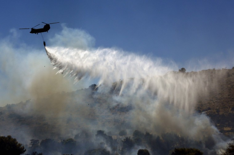 A Greek army helicopter drops water over a forest fire in Marathon near Athens. A wildfire fanned by strong winds raged near Athens on Monday, damaging homes and sending residents fleeing, fire brigade officials said. Reuters witnesses said the blaze had damaged at least three homes at a hamlet by the town of Marathon - the site of the historic 490 BC battle between Athenians and Persians about 40 kilometres (25 miles) northeast of the Greek capital. (Yannis Behrakis/Reuters)