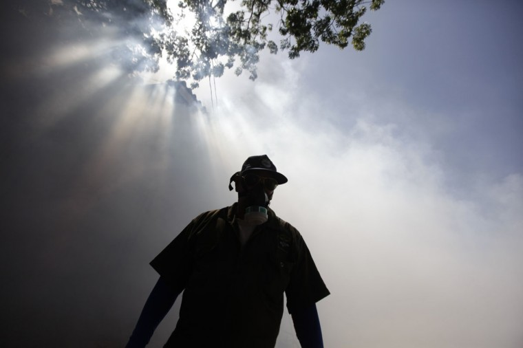 A health worker fumigates a school in Tegucigalpa August 9, 2013. Honduran officials said on Wednesday that 17 people have been killed and thousands more infected in an outbreak of dengue fever after a state of emergency was declared in the Central American country last month. (Jorge Cabrera/Reuters)